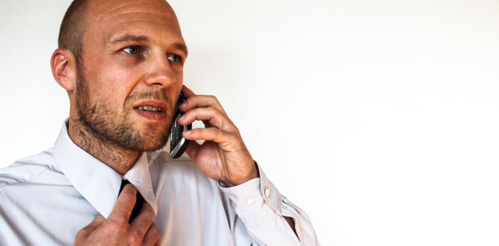 A man in a shirt and tie talks on the telephone for a job interview