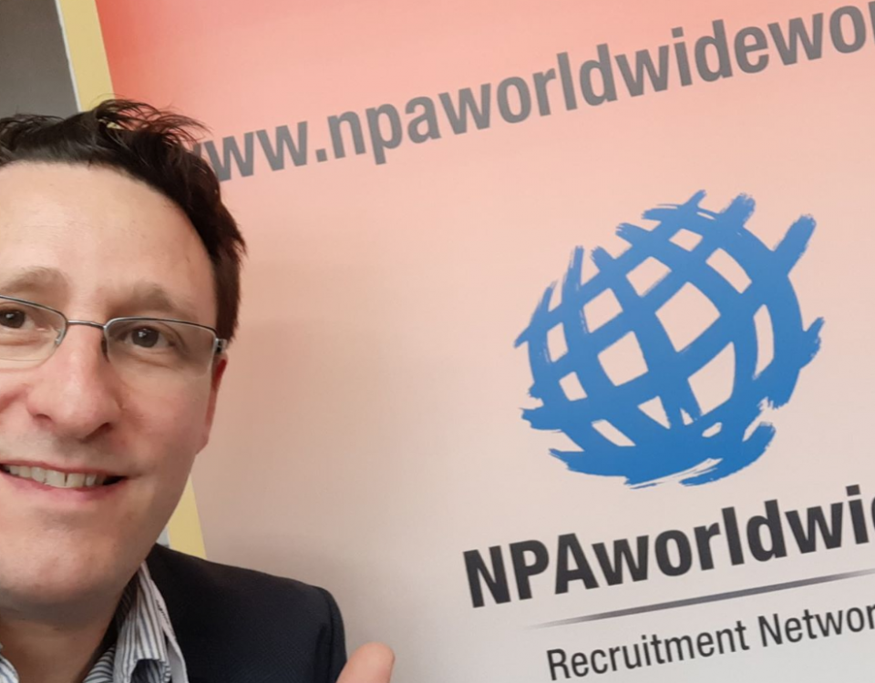 Macstaff MD Anthony McCormack stands next to a banner for NPA worldwide