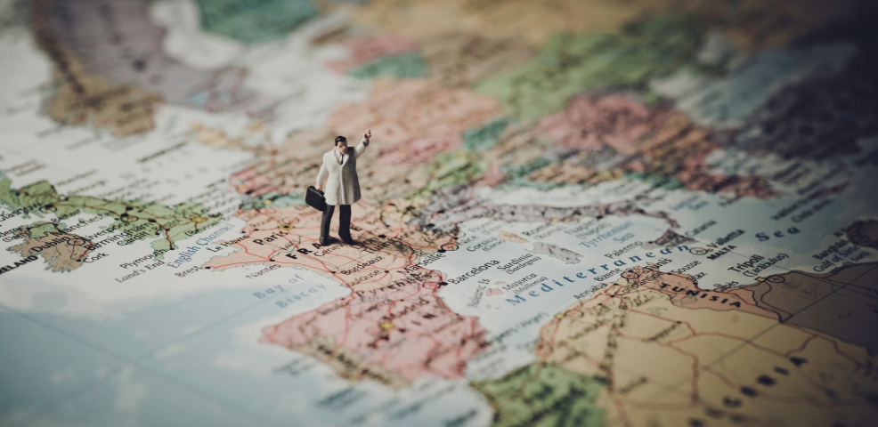 A small plastic figure dressed in a raincoat has his hand in the air on a map of Europe