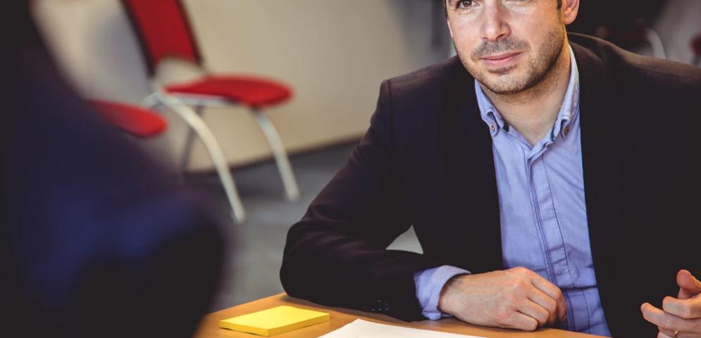 A man interviews someone across a desk