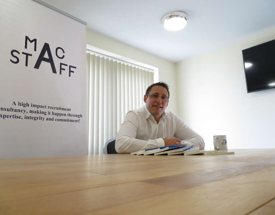 Anthony McCormack sits at a desk looking smart
