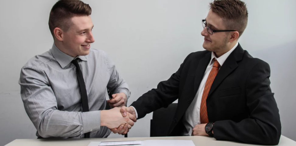 Two men in suits shake hands after an interview