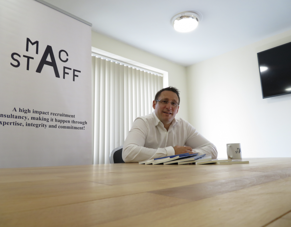 Macstaff MD Anthony McCormack sits at a desk with notes and a cup of coffee and discusses #MacstaffRepresents