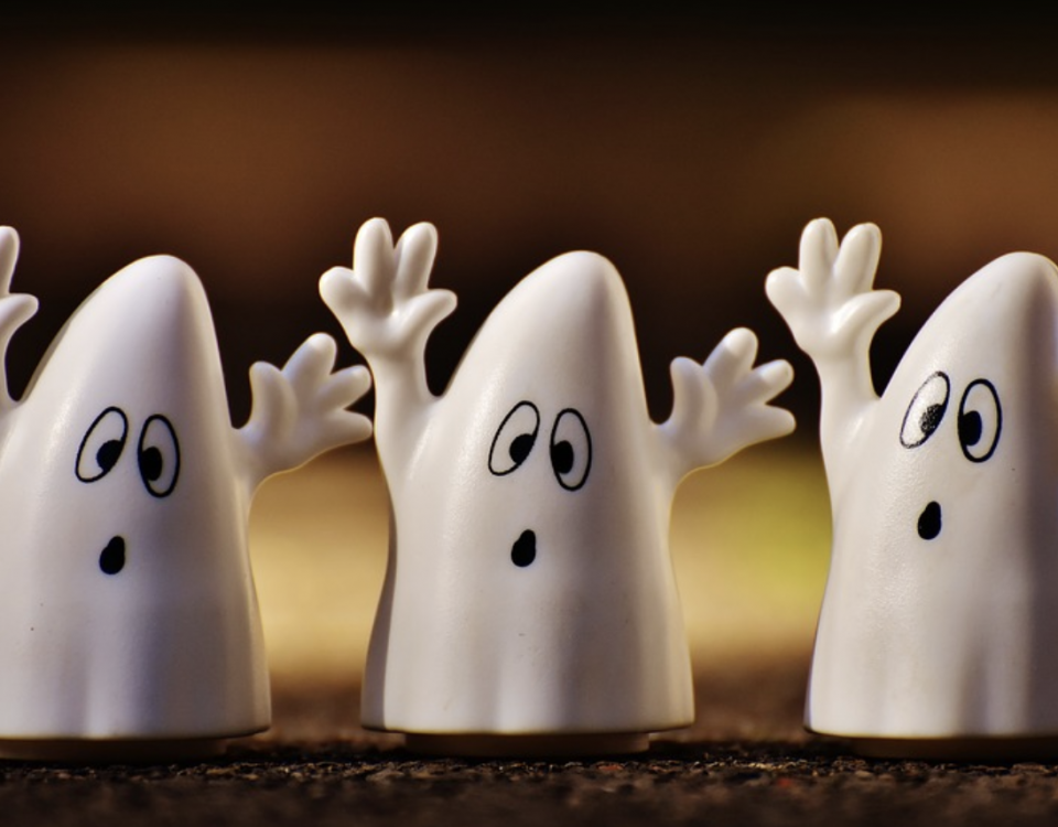 Three friendly looking ghosts wave their arms