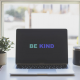 A computer has the words 'be kind' showing on it