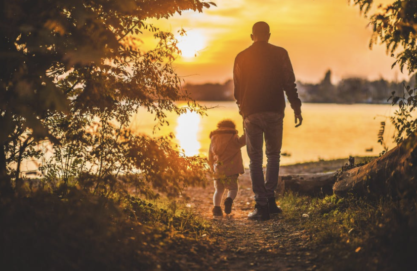A father holds hands and leads his child towards a lovely sunset