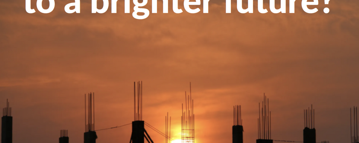 A picture of a construction site with the sun setting in the background